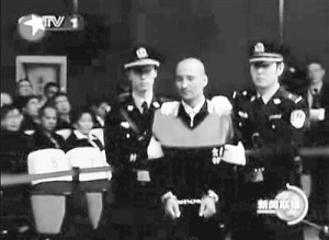 Defendant being brought into the courtroom in Monday's trial in Xinjiang